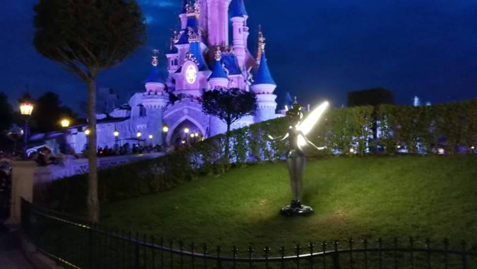 disneyland at night, a tinkerbell statue with glowing wings in front of cinderella's castle - disneyland bucket list
