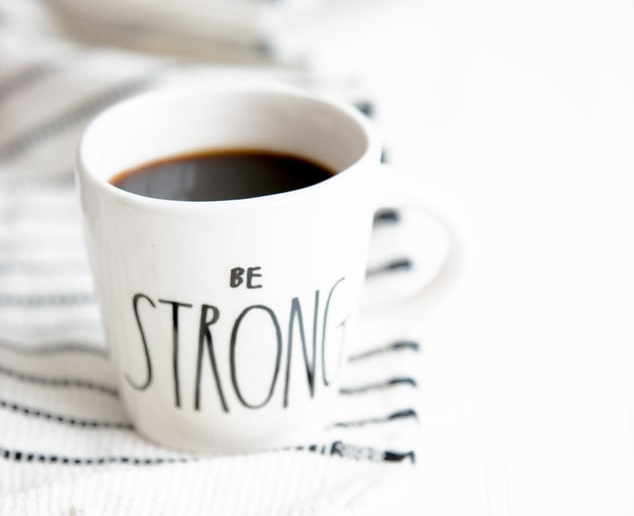 "mug of coffee that reads ""be strong"" HOW I MIND MY MENTAL HEALTH"