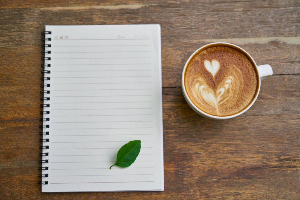 coffee and a notebook with a leaf on it - how to drink tea and coffee sustainably