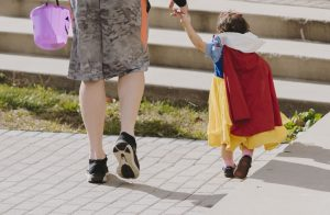 dad and daughter dressed as snow white trick or treating; green halloween