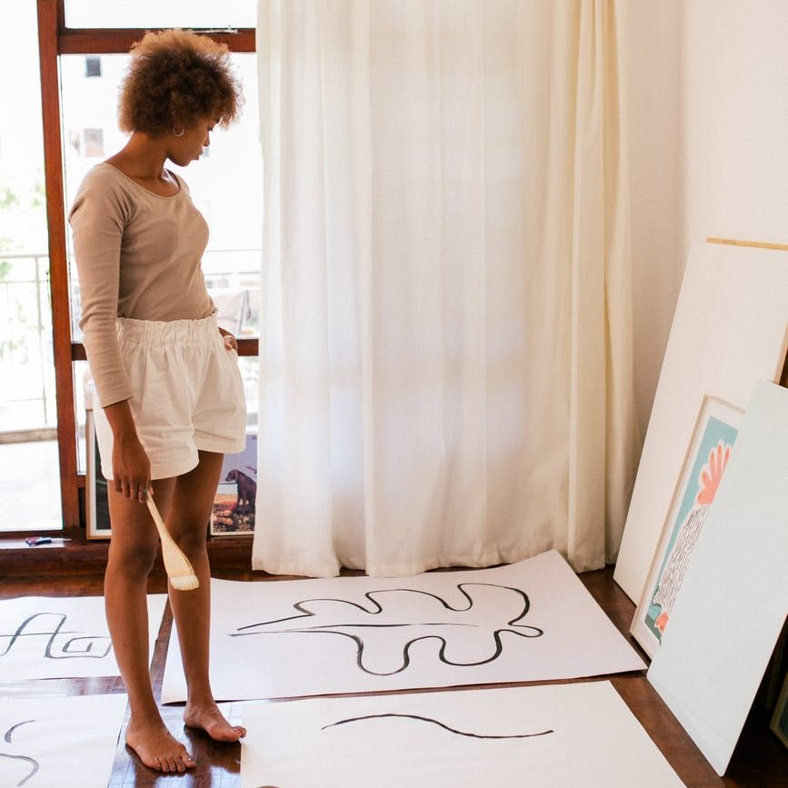 african american woman looking at paintings in studio