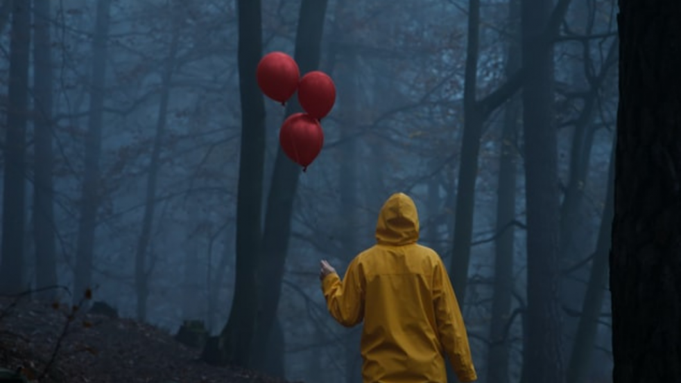man in yellow jacket with red ballons in forest, like IT