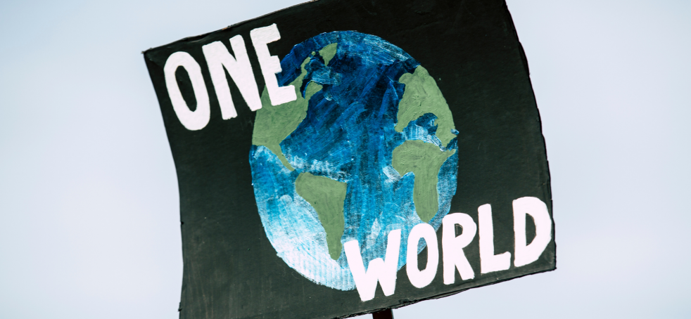 """""""One world"""" poster from protest as part of list on best climate change charities to donate to"""