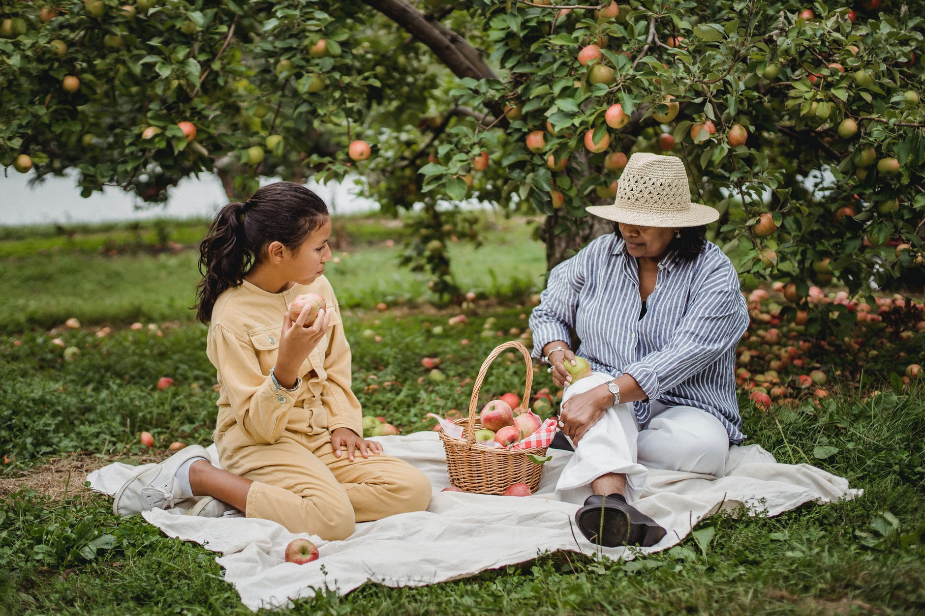 ethnic girl enjoying rest with mother in orchard